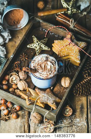 Mug of hot chocolate with whipped cream, cocoa powder, cinnamon, gingerbread cookies, nuts in wooden tray with Christmas decoration toys and pine cones over rustic wooden background, selective focus
