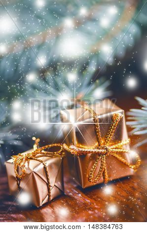 Christmas background, Gifts and spruce branches. Christmas presents on a wooden background. Soft focus. Sparkles and bubbles. Abstract background. Vintage