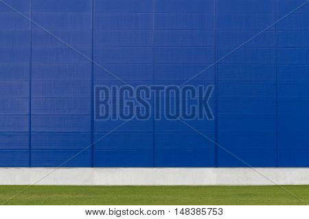 Mock up. Empty blue wall and green grass as background for photographers and design