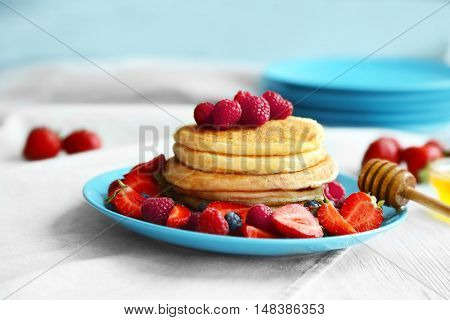 Tasty pancakes with fresh berries and honey on plate