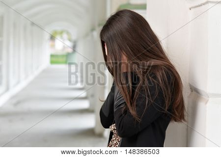 Girl with long hair standing in an old building with columns archway covering his face with his hands