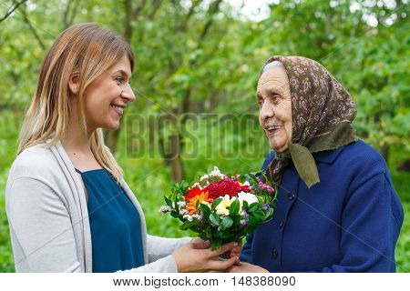 Happy old woman receiving flowers from her granddaughter
