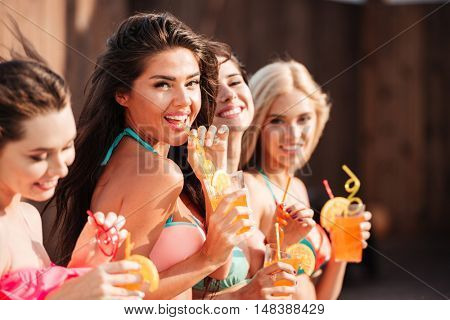 Group of happy lovely young women drinking cocktails in summer