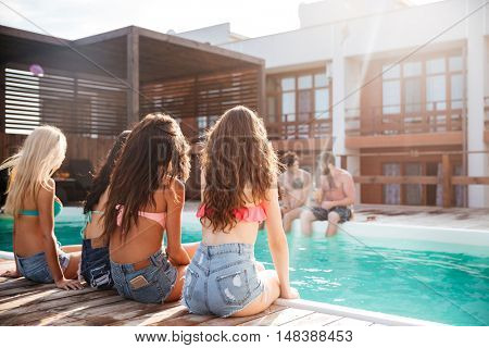 Back view of beautiful young women in swimsuit and shorts sitting near swimming pool