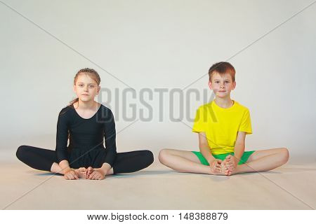little boy and girl doing yoga on white background