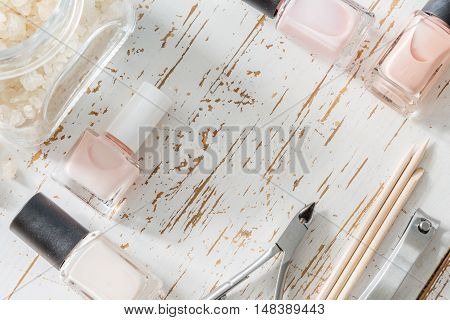 Selection of manicure tools on white wood background, copy space