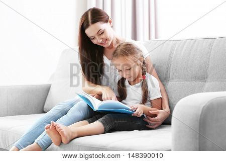 Happy mother with daughter reading book