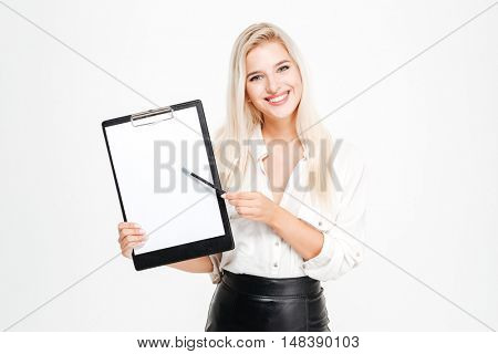 Cheerful young businesswoman standing and pointing on blank clipboard over white background