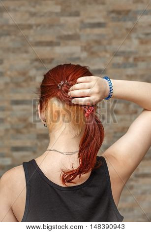 young model holding colored tail with hidden undercut bleached hair with elastic band arm. photo with shallow depth of field