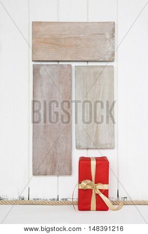 Red christmas present on old wooden shabby background for a xmas shopping concept, xmas card or mock up presentation.