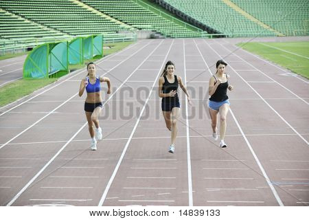 three athlete woman running on athletics race track on soccer stadium and representing competition concept in sport