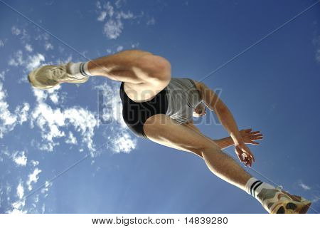 joven atleta corre y salta de altura con cielo azul y nubes en backgrond