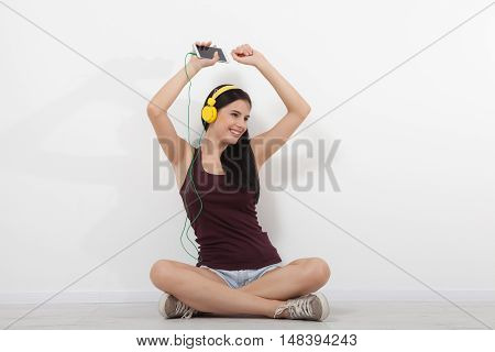 People, leisure and technology concept - happy woman or teenage girl in headphones listening to music from smartphone and dancing at home