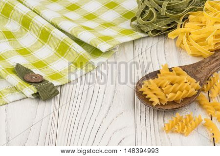 Pasta in a wooden spoon on old wooden table. Selective focus.