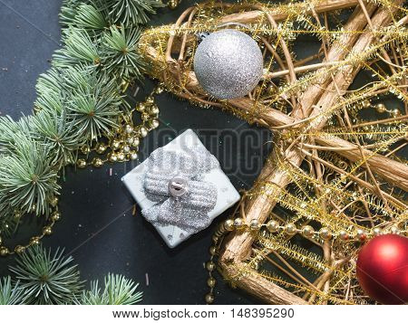 Blue spruce branches with decorative Christmas tree on dark black concrete effect background
