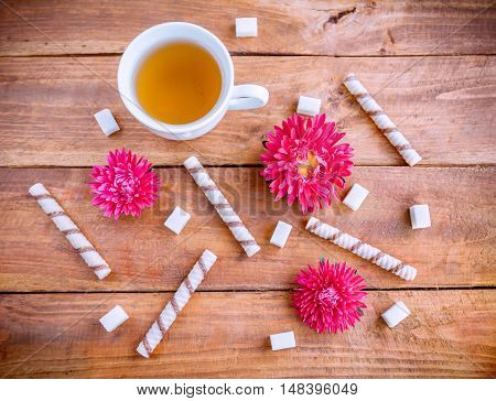 Green tea in a white cup, roll pastry, refined sugar and beautiful aster flowers on a wooden background.
