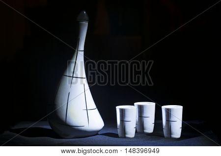 White porcelain jar on black background light brush