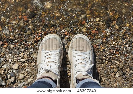 Sneakers with white laces on the feet in the water and stones