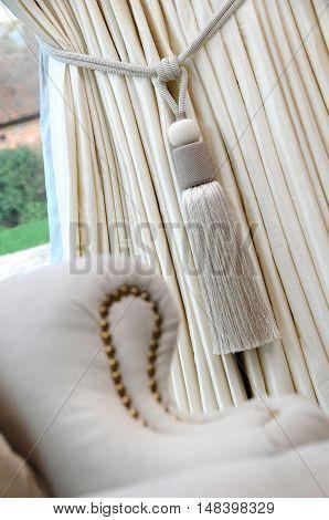 a cream coloured curtain tassle and curtain