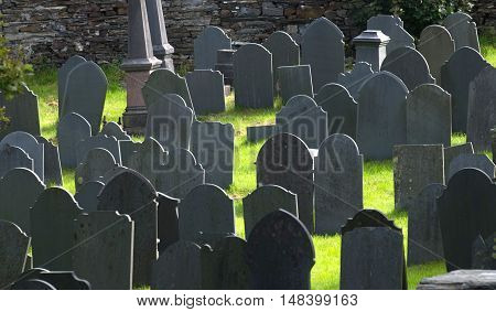 Grey grave stones backlight in church graveyard