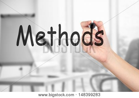 Human hand writing word METHODS at transparent whiteboard on conference hall background