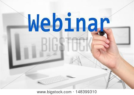 Human hand writing word WEBINAR at transparent whiteboard on conference hall background