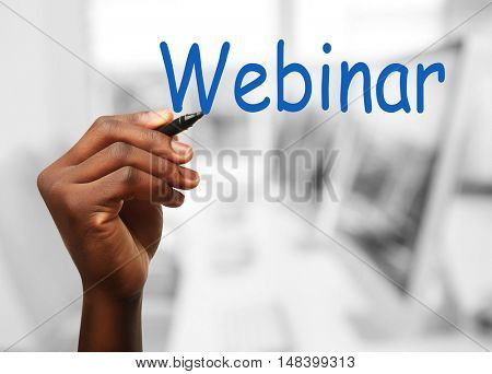 Human hand writing word WEBINAR at transparent whiteboard on blurred background