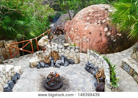 Burning a fire in the center of the circular seats on the background of stone pyramids