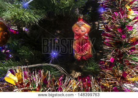 Christmas toys in the form of oriental girl on the background of tinsel and Christmas tree