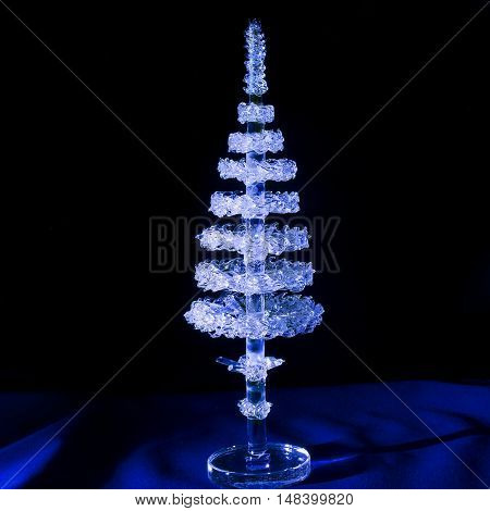 Air crystal figurine of spruce on a background of blue velvet, light brush