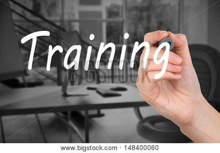 Human hand writing word TRAINING at transparent whiteboard on conference hall background