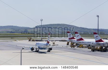 VIENNA, AUSTRIA - APRIL 30th 2016: Plane leaving terminal area on a busy Saturday at Vienna International Airport.