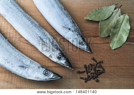 Frozen Pacific Saury on a wooden cutting board with spices (a bay leaf and cloves). Healthy eating. Fish preparation. Seafood with spices. Top view.
