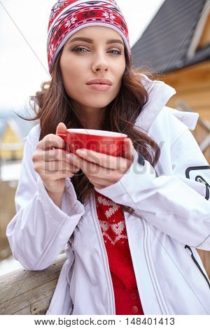 Young woman wearing a sweater and a white hat holding a cup of warm drink outdoors.