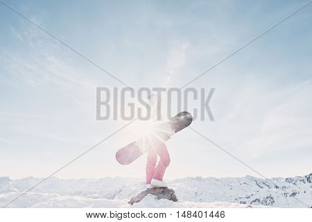 Side view of female snowboarder wearing colorful helmet, blue jacket, grey gloves and pink pants standing with snowboard in one hand and enjoying alpine mountain landscape - snowboarding concept