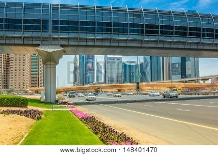 Dubai, United Arab Emirates - May 1, 2013: close up of Dubai Financial Centre Metro station and footbridge. Underground lines without a driver in the Dubai metro. Traffic on Sheikh Zayed Road.