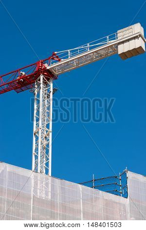 Detail of a construction site with red and white crane and a scaffolding with a white safety net on blue sky