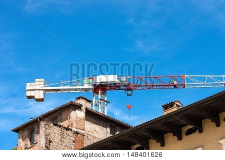 Detail of a construction site with a red and white crane and old house on a clear blue sky