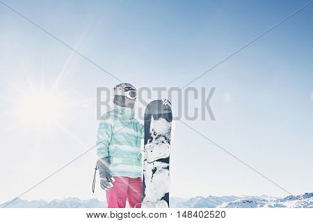 Female snowboarder wearing colorful helmet, blue jacket, grey gloves and pink pants standing with snowboard in one hand and looking at beautiful alpine mountain landscape - snowboarding concept