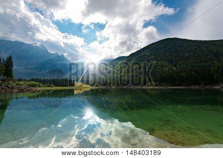 Lago di Fusine (Fusine Lake). Small mountain lake with sun rays in Julian Alps Tarvisio Friuli Venezia Giulia Italy