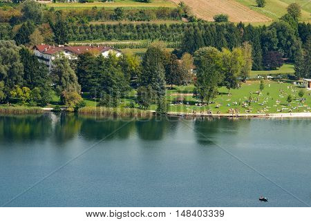 Coast of Levico Lake (Lago di Levico) with tourists swimmers and people sunbathers. Levico Terme Trentino Alto Adige Italy Europe
