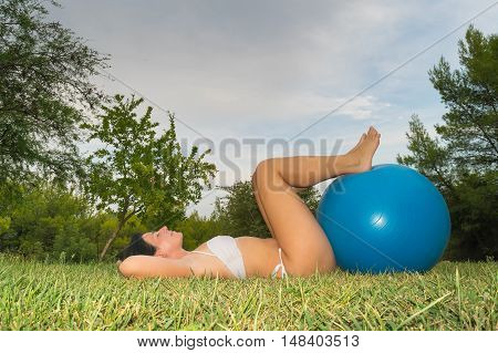 Woman relaxing doing some pilates exercises with a fitball.