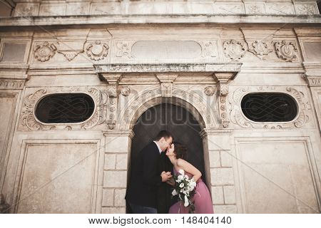 Gorgeous wedding couple, groom and bride with pink dress walking in the old city of Krakow.