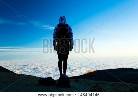 Woman successful hiking climbing silhouette in mountains motivation and inspiration landscape on island and ocean. Female hiker on mountain top looking at beautiful clouds view on Tenerfie Spain.