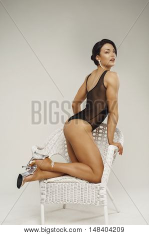 Fitness girl on a white wicker chair dressed in a black body on white background