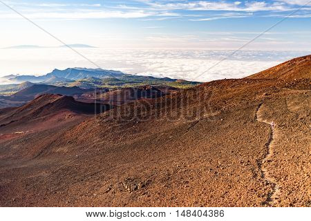 Inspirational landscape view with woman running in mountains on rocky trail sunny summer day. Beautiful ocean and island landscape with rocky volcano trail footpath on Tenerife Canary Islands.