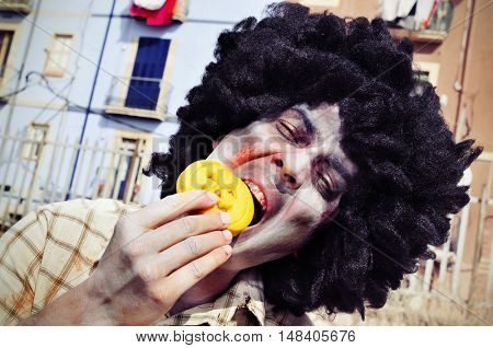 closeup of a scary zombie with an afro hairdo eating a pumpkin-shaped cookie