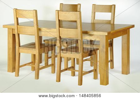 A wooden dining table and four wooden chairs on a white background