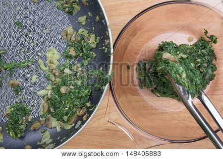 Putting cooking spinach to bowl / cooking Baked spinach concept