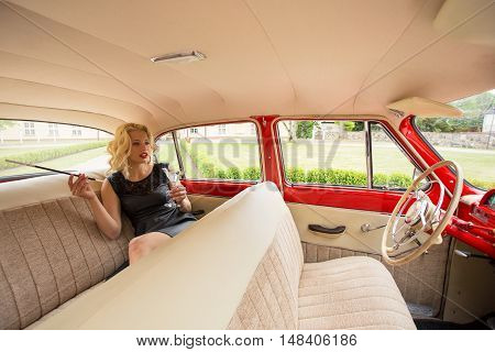 Woman sitting in the backseat of retro car